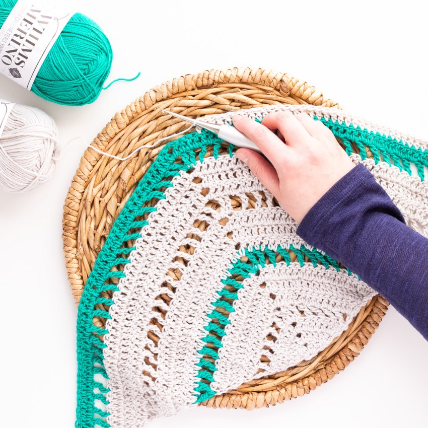 hand holding a silver furls hook, crocheting a striped triangle shawl