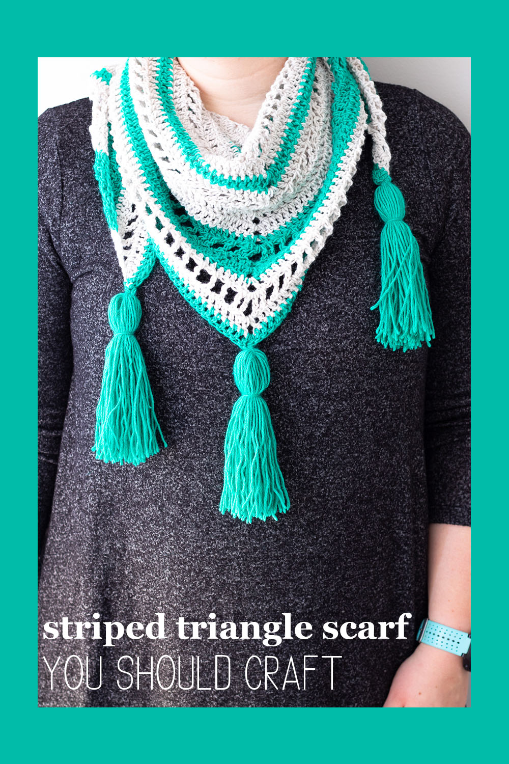 woman wearing a dark grey dress and teal striped triangle scarf - crochet pattern from you should craft