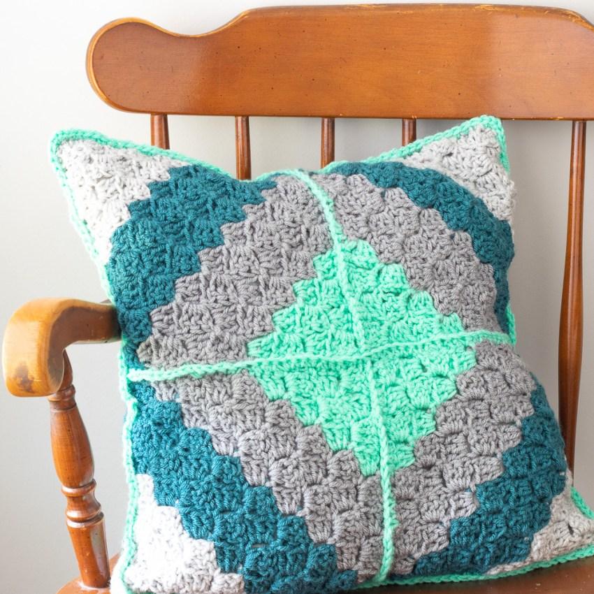 diamond corner-to-corner crochet pillow on a wooden chair