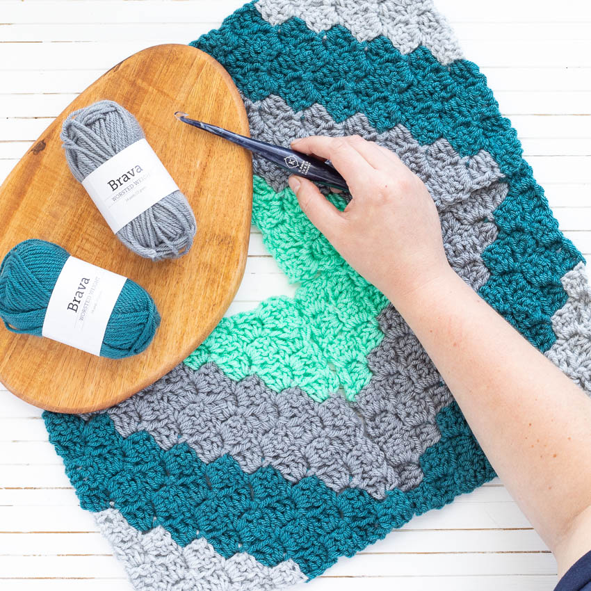 corner-to-corner crochet squares with yarn and a hand holding a furls crochet hook