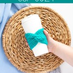 """hand holding a reusable coffee cup with a teal crochet sleeve. text overlay says """"twisted cup cozy - free crochet pattern from you should craft"""""""