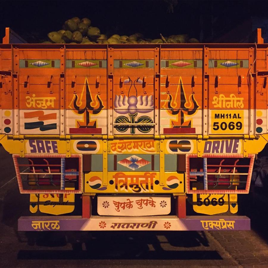Coconut delivery truck being unloaded at night.