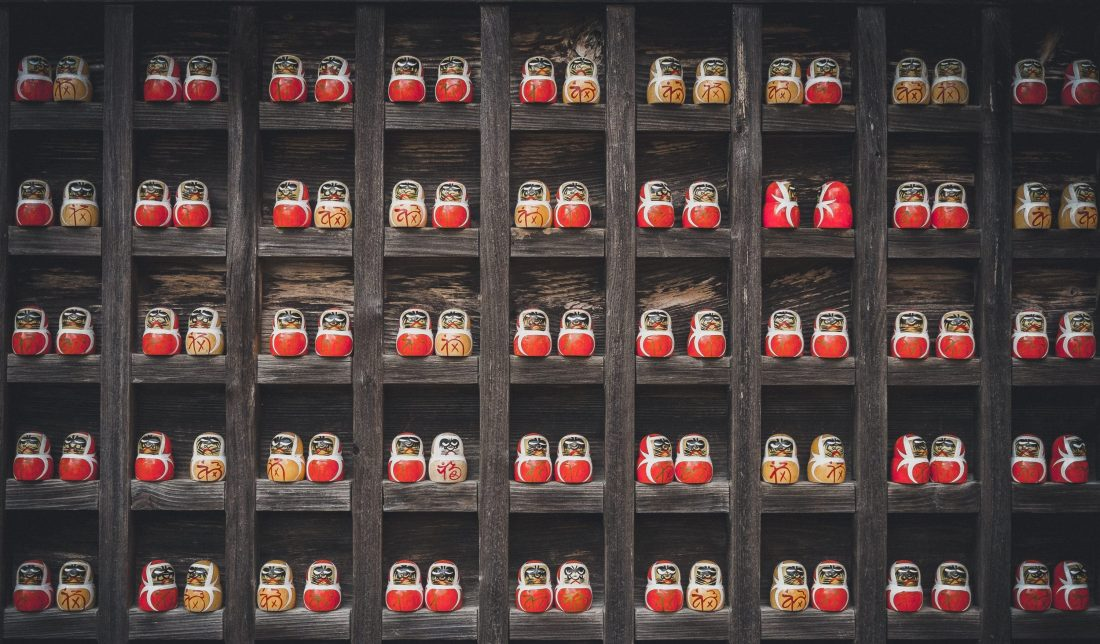 A shelf grid of many Russian nesting dolls