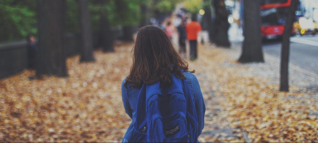 Girl wearing backpack facing away walking down a street in autumn