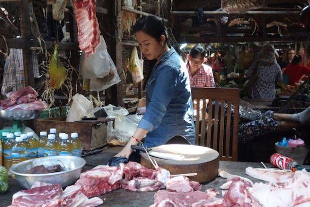 Devant un stand de viande sur le marché de Kampot au Cambodge. Photo yoy tour du monde http://yoytourdumonde.fr