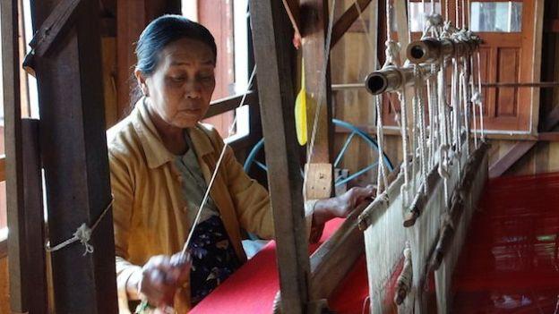 Une magnifique femme birmane entrain de tisser dans une fabrication à meme le lac inle en birmanie photo blog voyage tour du monde http://yoytourdumonde.fr