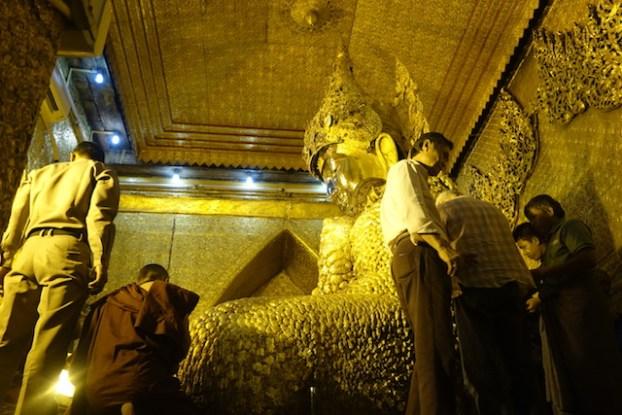Dans la Pagode de Mahamuni à Mandalay les fideles apportent des feuilles d'or qu'il depose sur le corps du Bouddha. Plus de 15cm d'epaiseur d'or sur le corps du Bouddha photo blog voyage tour du monde http://yoytourdumonde.fr