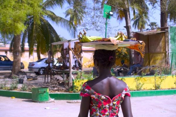 Une femme porte des bananes pour les vendres dans les rues de Ziguinchor au Sénégal en Casamance photo blog voyage tour du monde http://yoytourdumonde.fr
