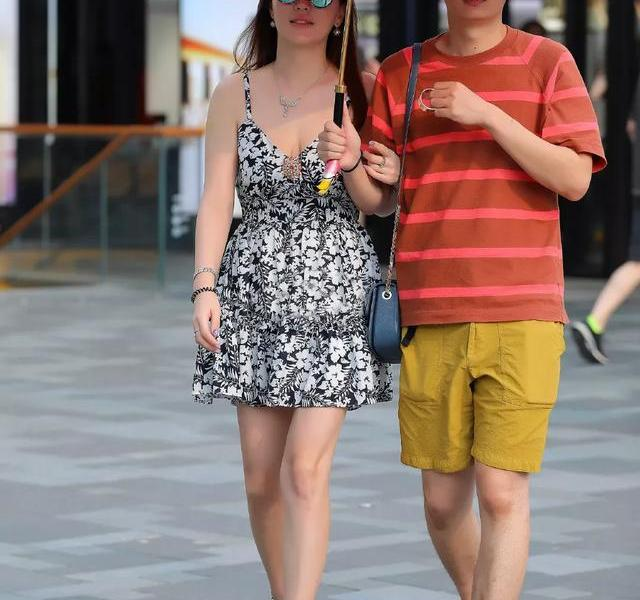 The photographer shoots a couple of couples shopping together on the street. The girl looks bright and beautiful, her skin is white, delicate and shiny, and her hair is shaggy and thick, exquisite and beautiful. The girl is wearing a fashionable floral suspender dress, the delicate small floral pattern is beautiful and generous, and the visual effect is excellent. The fashionable sling is slender and stylish, highlighting the charming shoulder skin of the lady. The unique small V-neck shape is very Good show the bright and delicate skin of the girl's neck