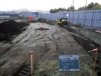 敷き均した土を締め固めている様子。