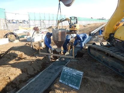 ①側溝の基礎となるコンクリートを打設している様子