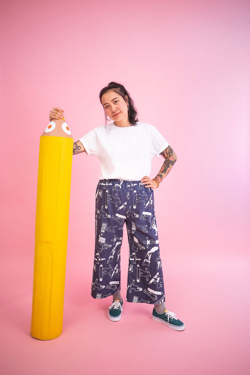 Becky wears a crisp white t-shirt with wide leg all over print denim trousers made by YUK FUN and posing with a giant yellow pencil