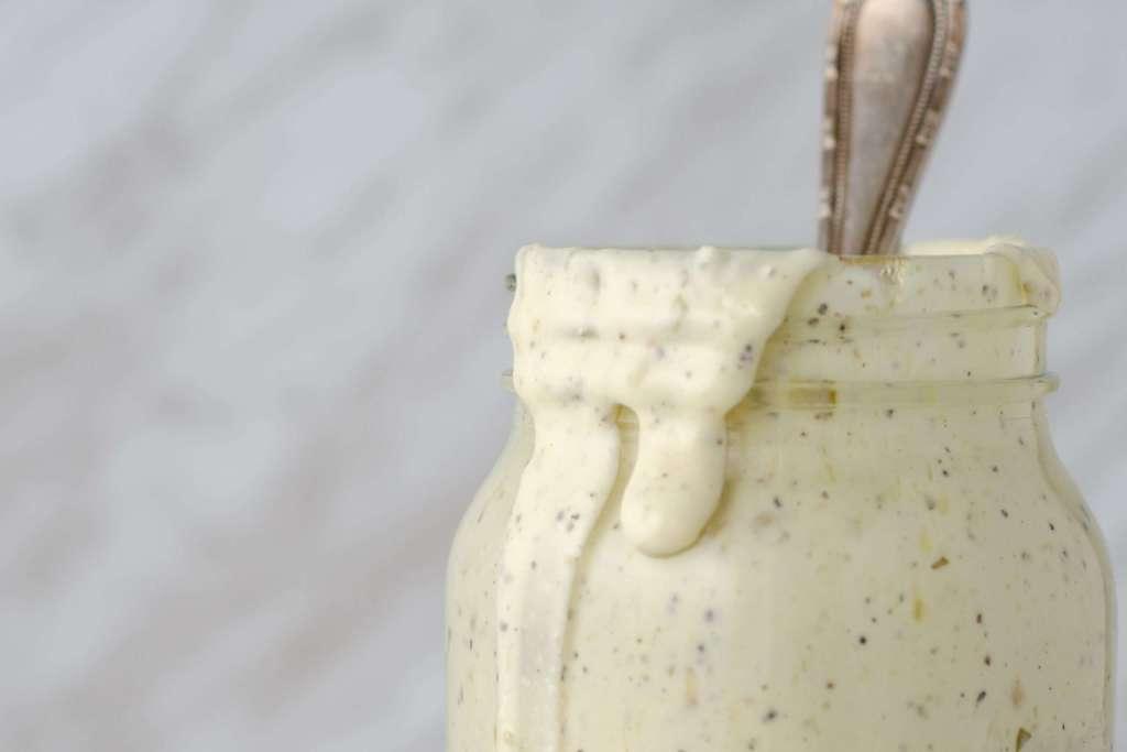 Cream Mason jar keto Caesar dressing dripping down a jar