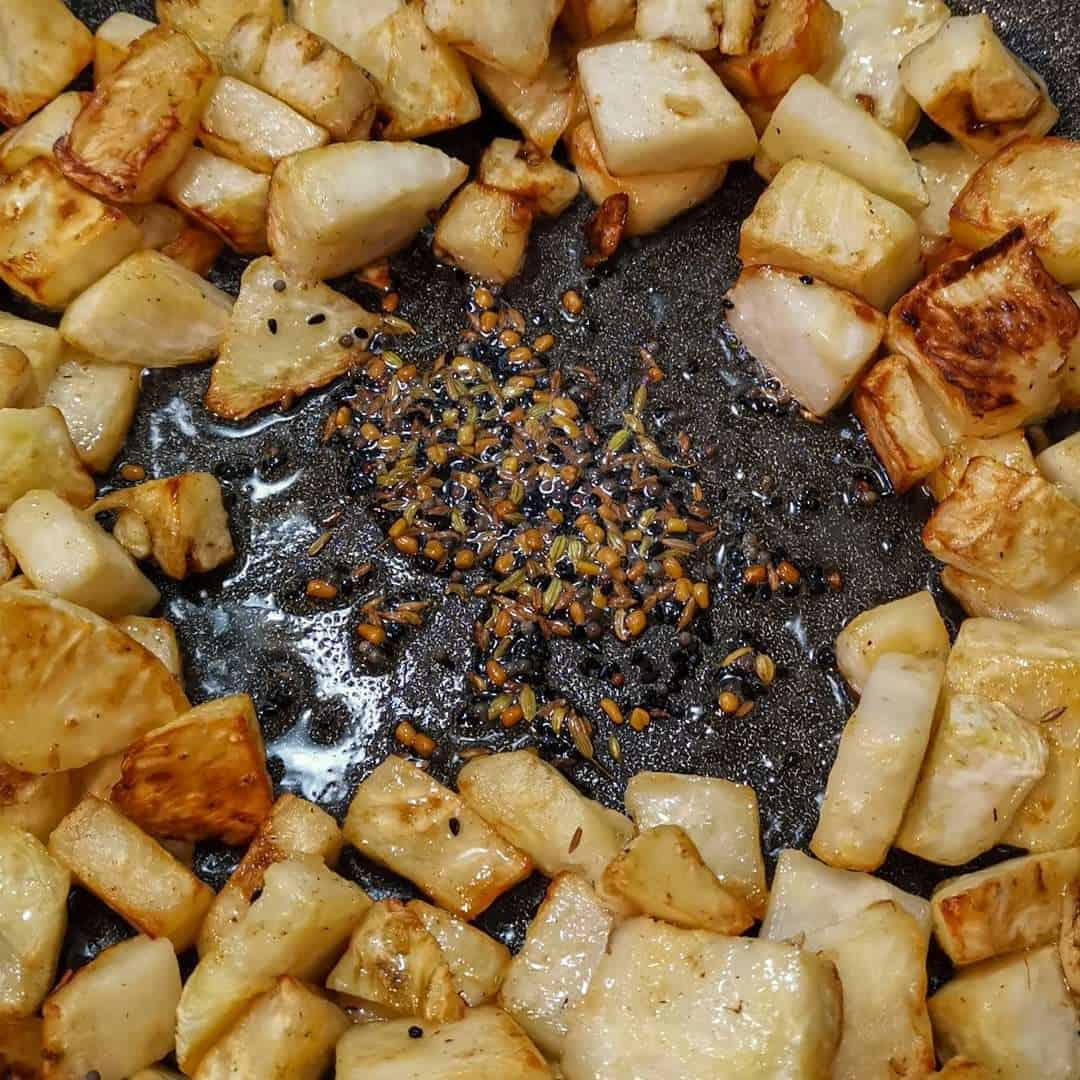 A well is formed in celeriac to expose the hot [an and temper Indian spices