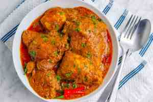 Spicy keto butter chicken looking mouthwatering in a white bowl on a marble surface