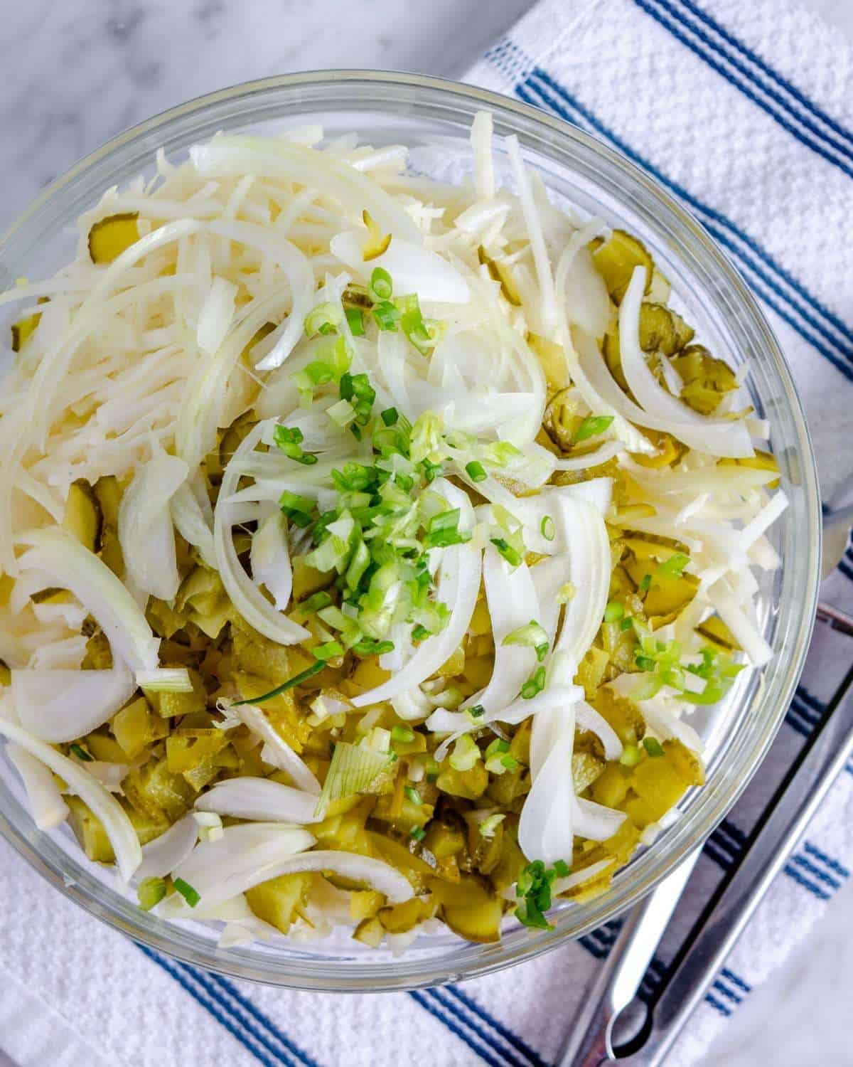 Low carb coleslaw with dill pickles, and onions in a bowl