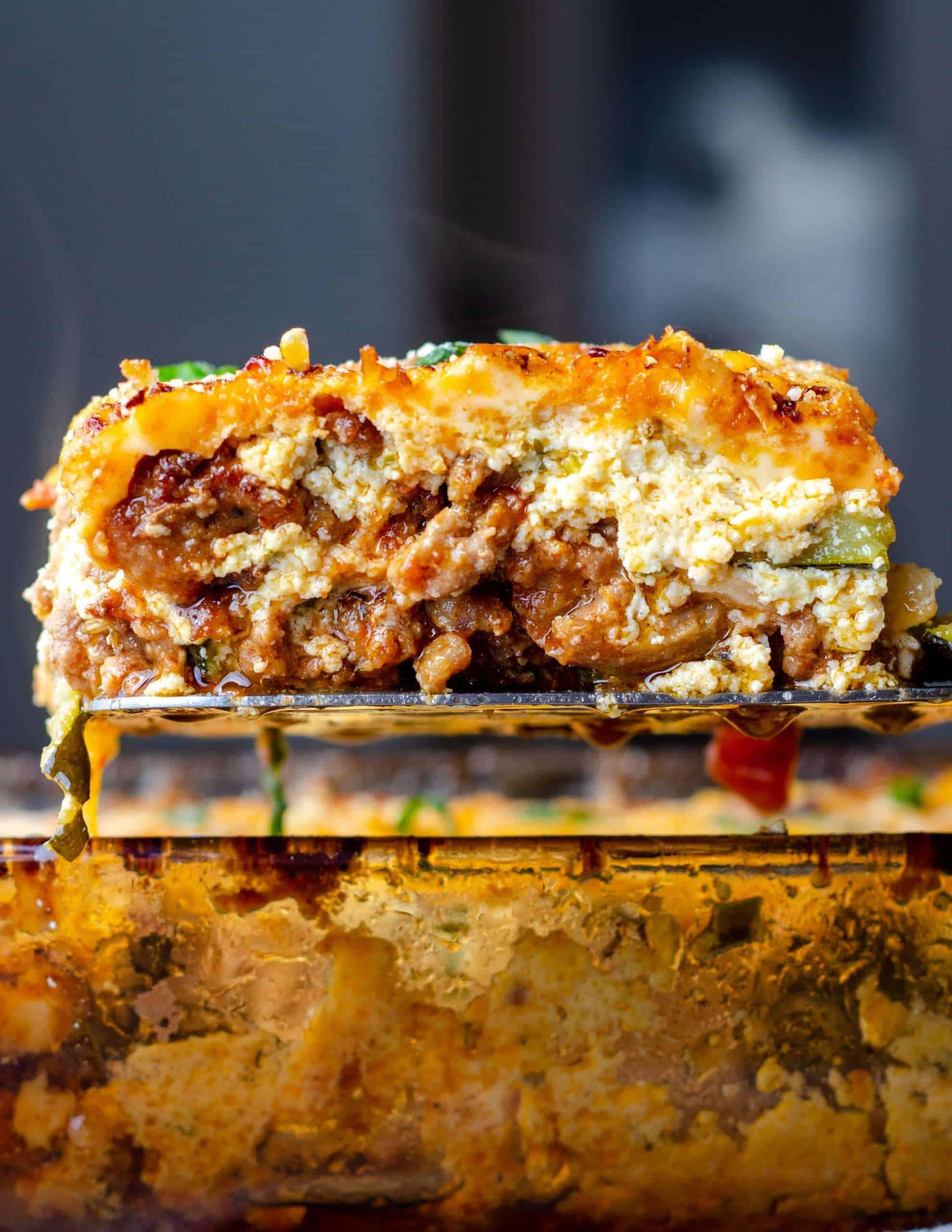 keto zucchini lasagna on a spatula over the pan