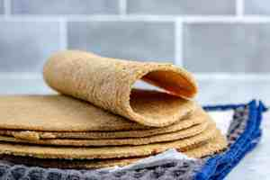 A stack of keto oat fiber and almond flour tortilla with a folded tortilla on top