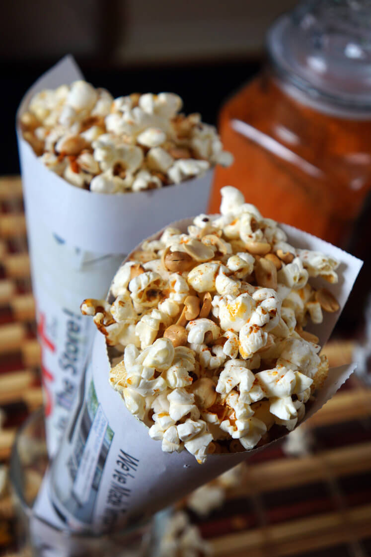 Nigerian Spicy Popcorn and Peanuts (Guguru and Epa) served in newspaper with a sprinkle of pepper