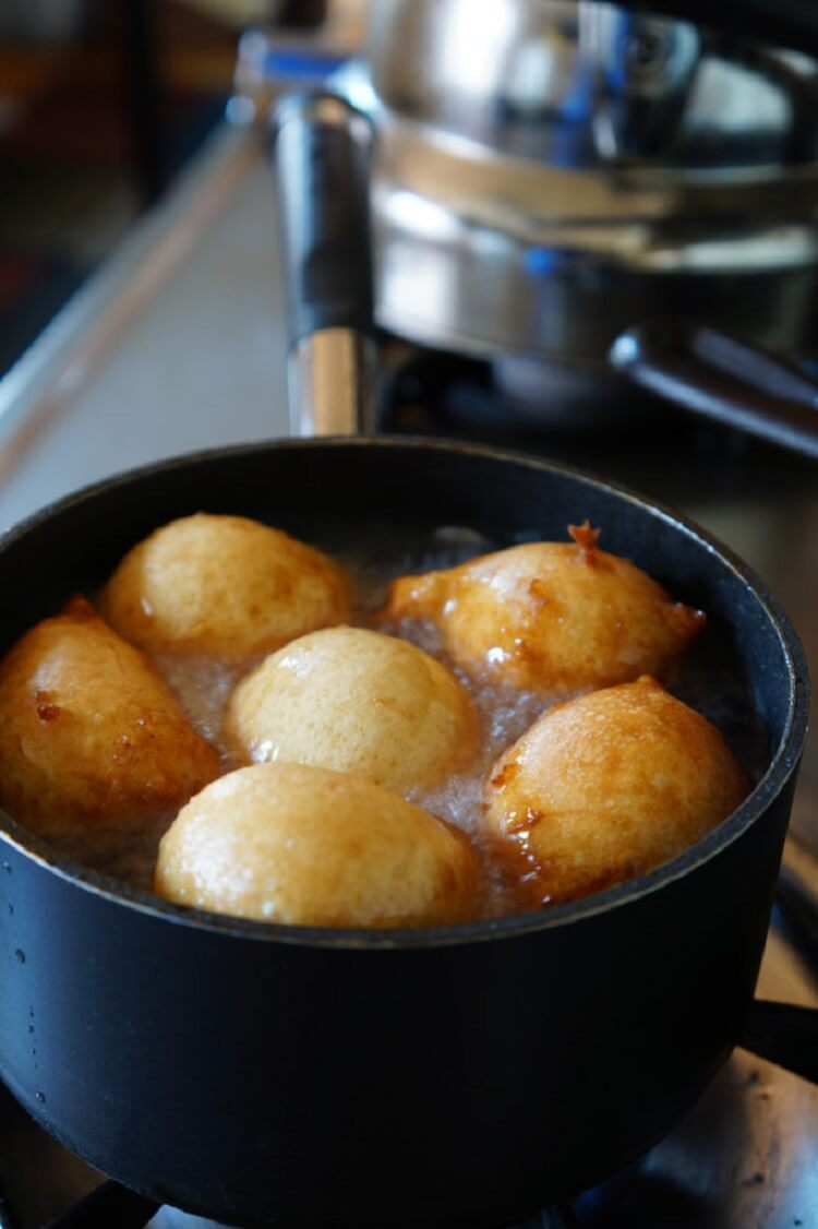 puff puff browned on one side in a pot of oil
