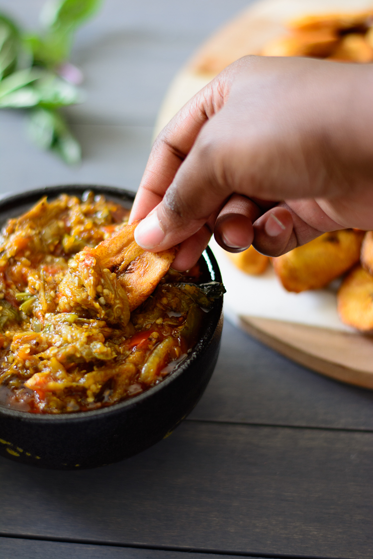 A hand scooping up some garden egg stew (eggplant sauce) with plantain