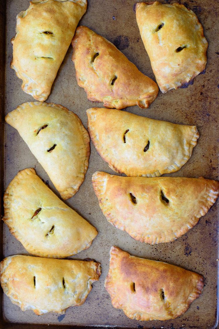 Secrets to a stable and flaky meat pie crust - top view of meat pies on a pan