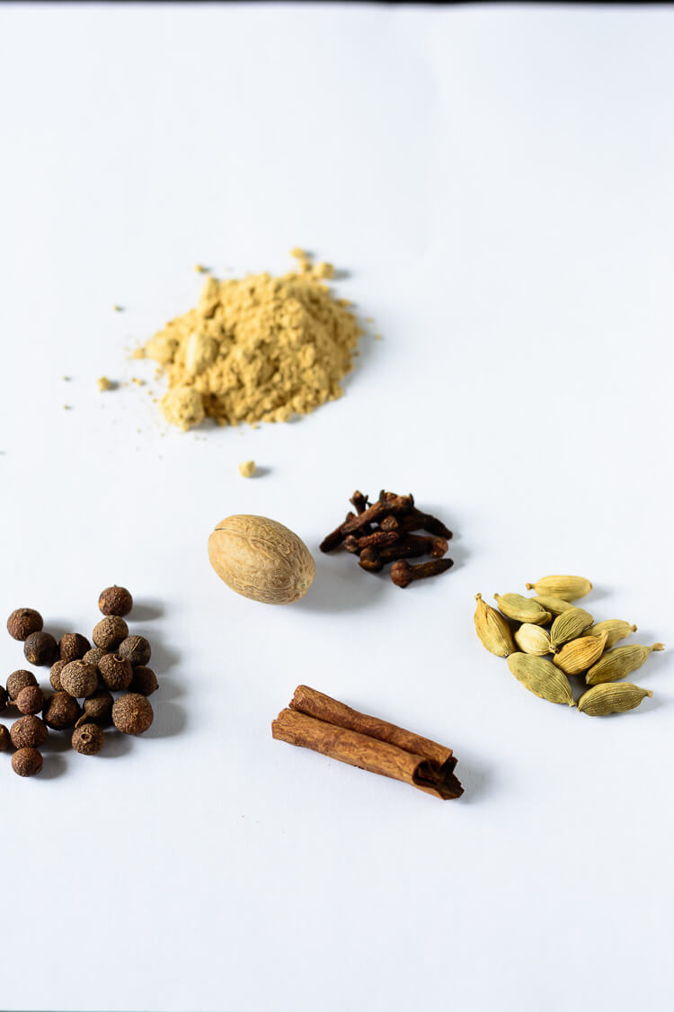 ginger powder, green cardamom pods, cinnamon, nutmeg, allspice berries, cloves on a table