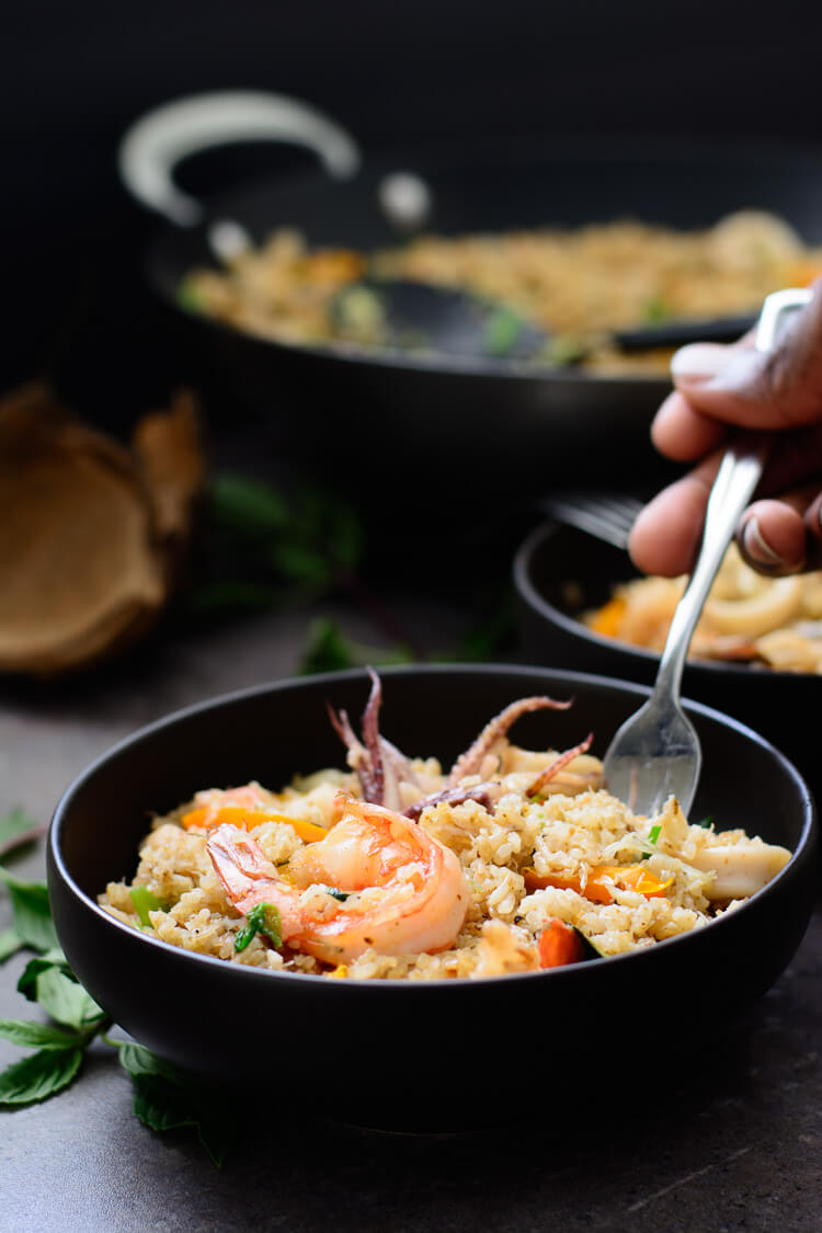 Mixed seafood coconut fried rice  served in plate with fork