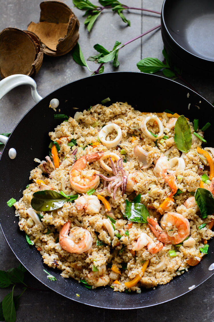 Coconut Seafood Fried Rice (Fisherman's Rice) - beautiful overhead shot of the entire fried rice in a wok with coconut husks on the side