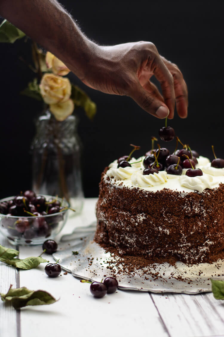 black forest cake with hand adding a piece of cherry to the top