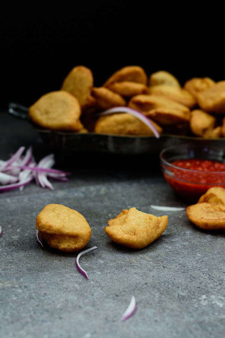 Nigerian Akara Recipe (Accara/Acaraje): Black Eyed Pea Fritters - 3 bean fritters in foreground with kaani dipping sauce and bundle in the back