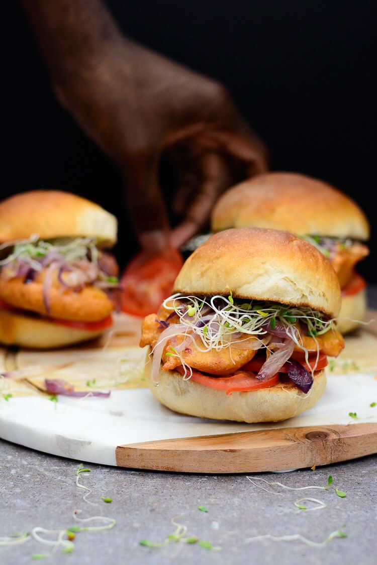 Nigerian Akara Recipe (Accara/Acaraje): Black Eyed Pea Fritters - 3 Akara burgers with hand picking tomato in the background