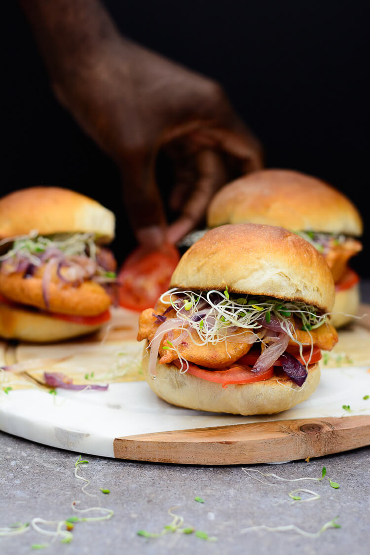 3 Akara burgers with hand picking tomato in the background