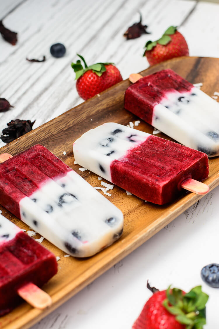 Mixed Berry & Hibiscus Coconut Milk Popsicles - popsicles arranged on a wooden tray