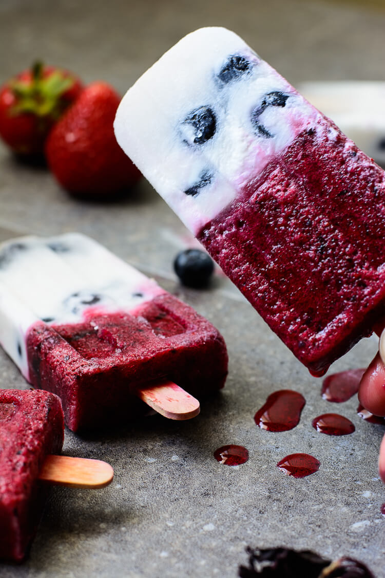 Mixed Berry & Hibiscus Coconut Milk Popsicles - hand holding a delicious popsicle up