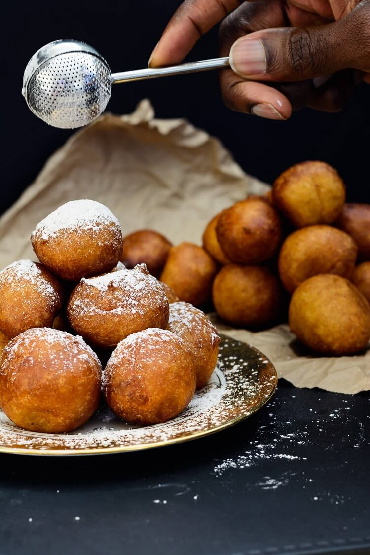 Sprinkling pumpkin spice sugar on Nigerian Puff Puff with pepper and pumpkin