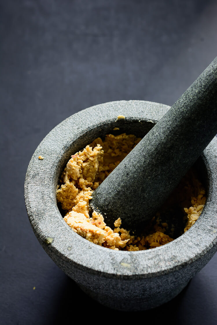 Miyan Taushe: Nigerian Pumpkin Stew - Peanuts ground in a mortar with a pestle