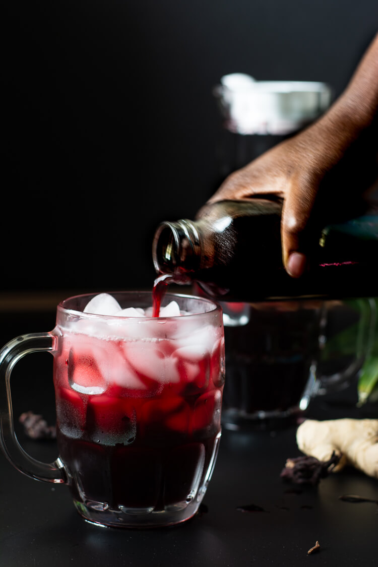 hand pouring zobo drink into glass cup