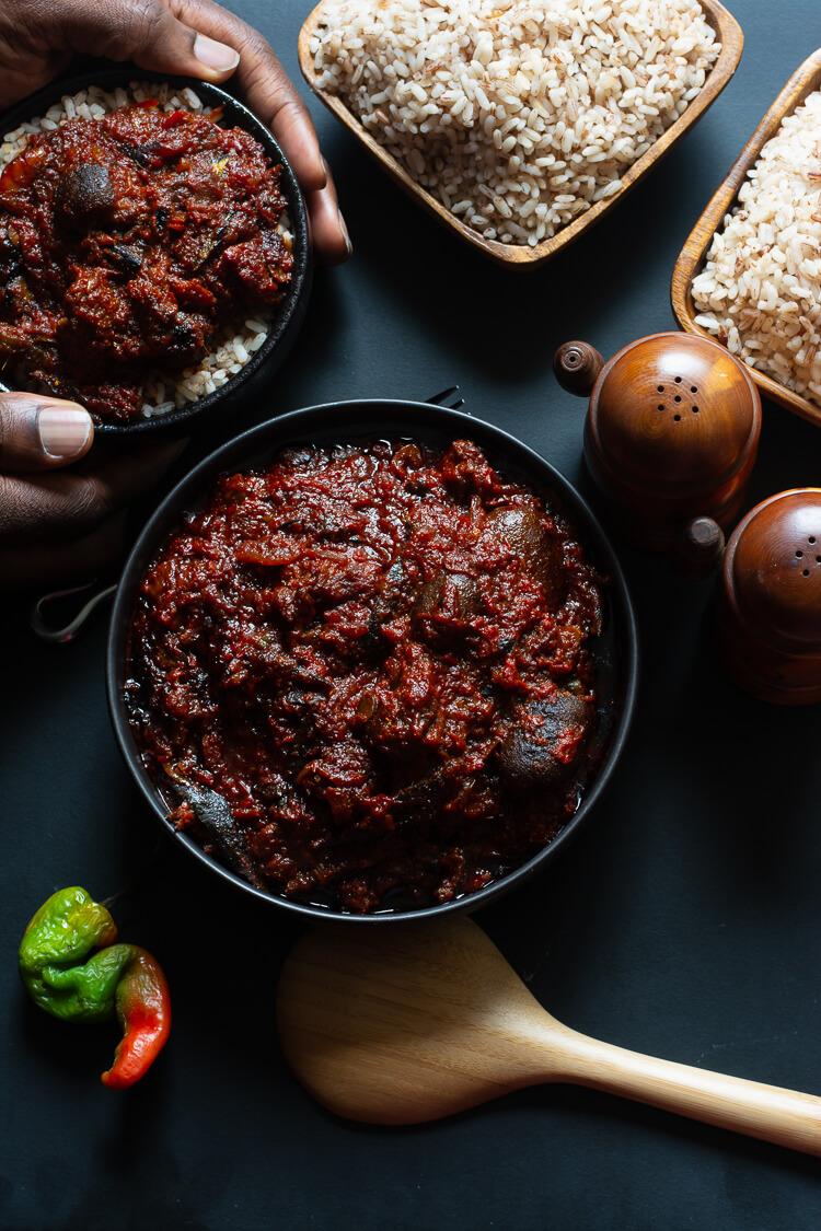 How to Make Ofada Stew (Nigerian Ofada Sauce Recipe) - top view of one dished bowl of ofada rice and stew and another held by two hands with two wooden bowls of ofada rice on the side