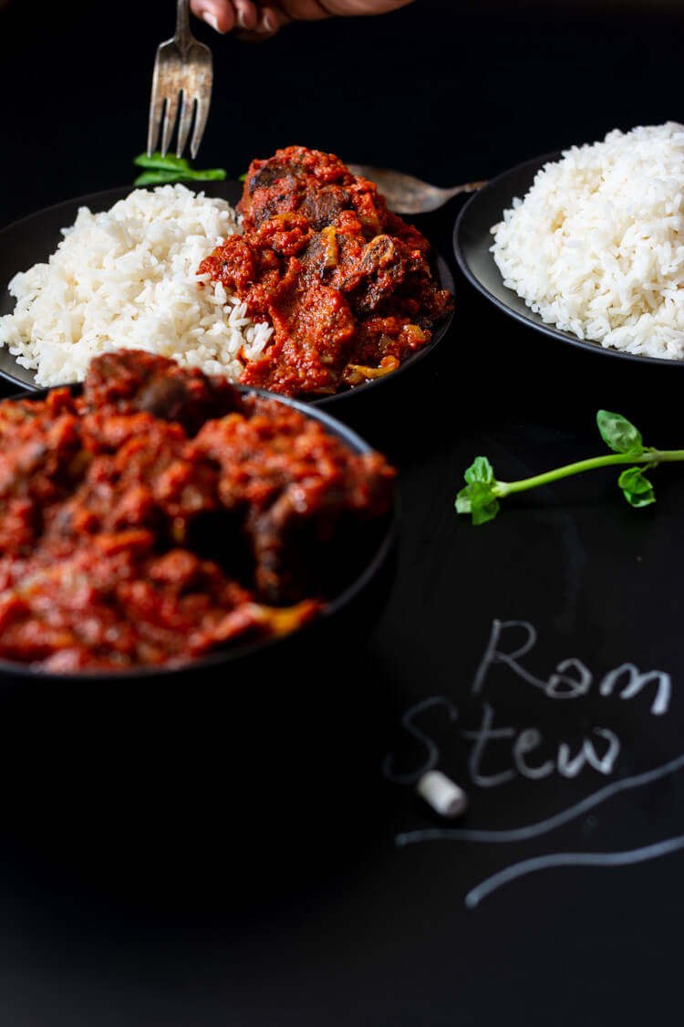 Focus on plate of rice and tomato stew and ram meat in background with bowl of stew in foreground
