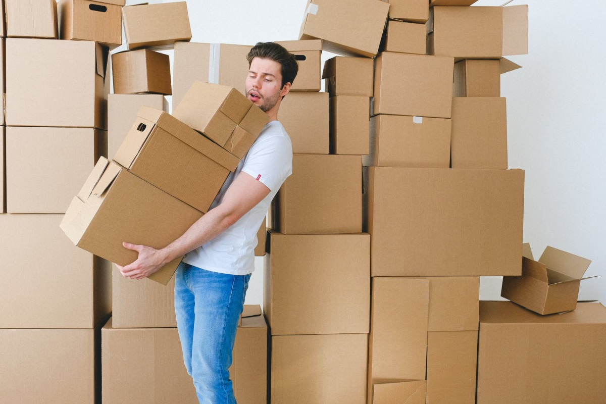young man carrying heap of cardboard boxes during relocation in new flat