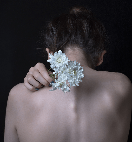 Woman with naked back holding a flower over her spine.