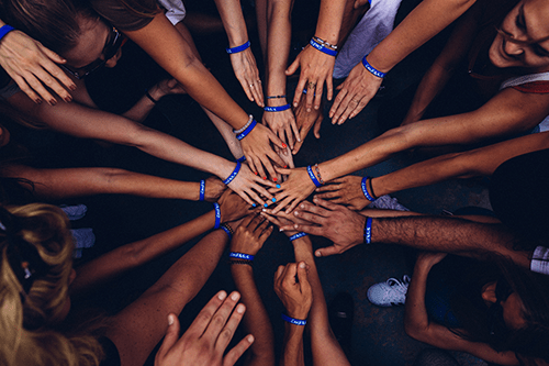 Circle of hands touching.