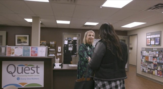 A doctor greets her patient in a clinic reception area.