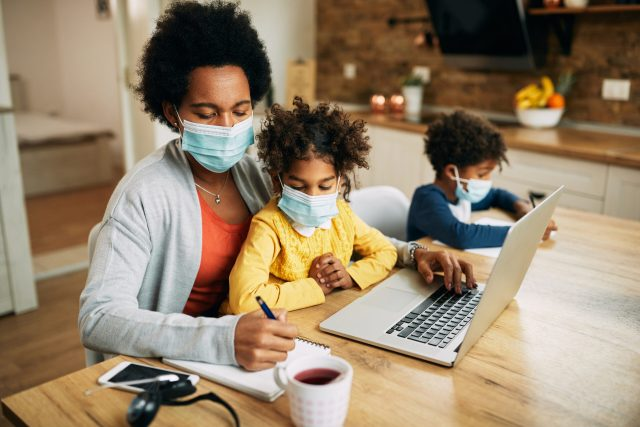 Black single mother with kids working at home due to coronavirus pandemic.