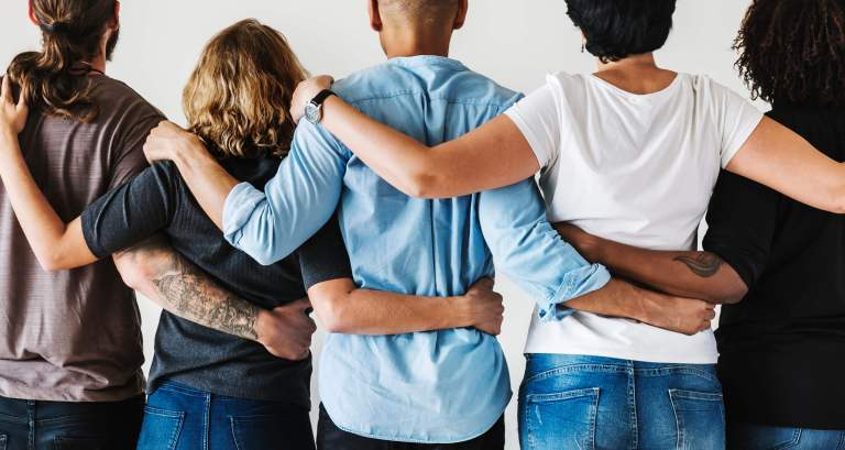 multiethnic adults with arms around each other's shoulders facing away