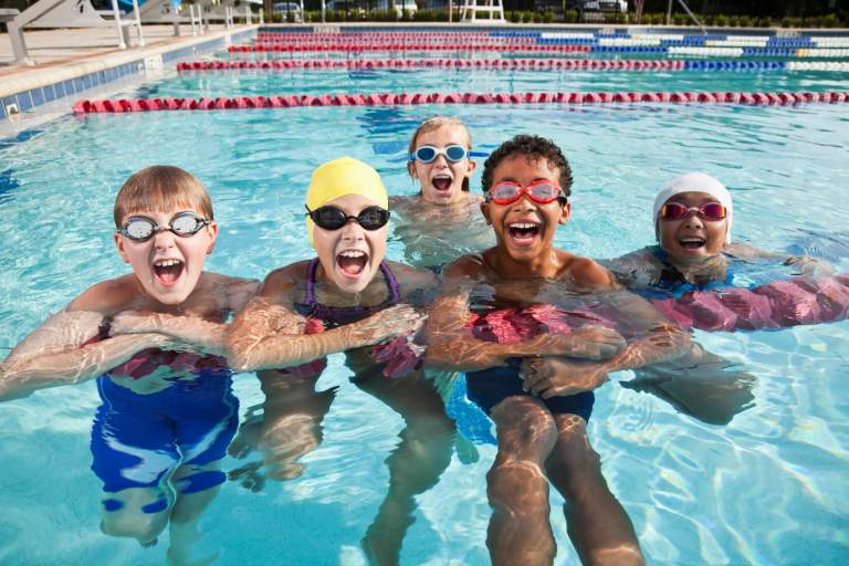 Group of multi-ethnic children having fun in swimming pool.