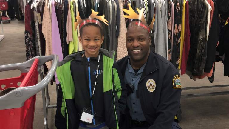 Young child and police officer pose looking at the camera and smiling