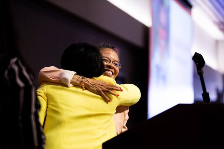 Phyllis Goff hugging Shawnterra Hardy onstage at Sweet Success