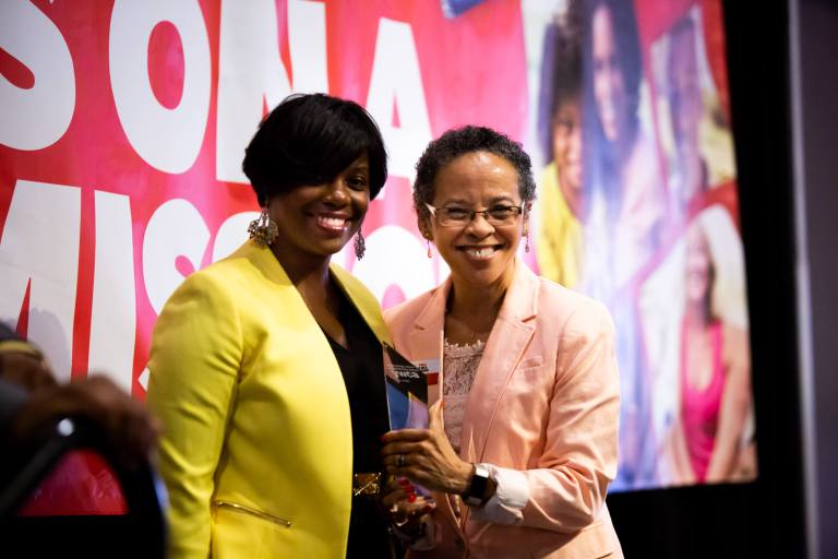 Phyllis Goff and Shawnterra Hardy, two African-American women, smiling onstage at Sweet Success after receiving an award.